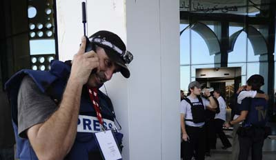A journalist talks on his satellite phone outside the Rixos Hotel in Libya in August 2011. (AFP/Filippo Monteforte)