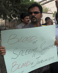 A Pakistani journalist holds a sign at a protest against Shahzad's murder in Karachi last year. (AFP/Rizwan Tabassum)