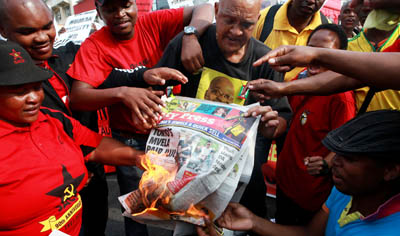 Protesters burn a copy of the City Press newspaper. (AFP/Rajesh Jantilal)