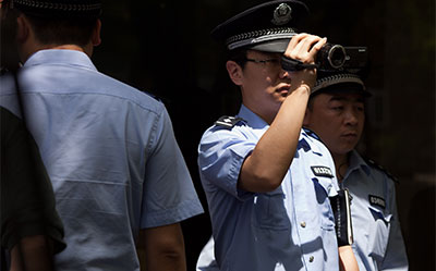 A police officer films members of the press gathered outside the Beijing hospital where Chinese activist Chen Guangcheng was staying on May 3. (AFP/Ed Jones)