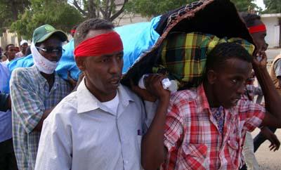 Des journalistes Somaliens portent le corps de Abdisalan Sheikh Hassan qui travaillait pour la chaine Horn Cable TV et a été tué en décembre 2011. Peur de la violence est une des raisons qui poussent le plus les journalistes en exil. (AFP/Mohamed Abdiwahab)