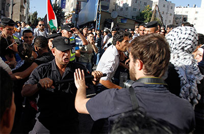 A member of the Palestinian security forces scuffles with a journalist in Ramallah Sunday. (Reuters/Mohamad Torokman)