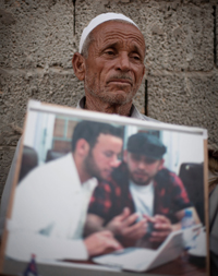 Abdala Fassouk, the father of Abdelqadir Fassouk, holds a picture of the two cameramen. (AP/Manu Brabo)