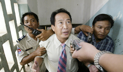 Radio journalist Mam Sonando, seen here with police in court in 2005, was charged with anti-state activities on Monday. (Reuters/Chor Sokunthea)