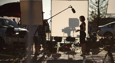 A TV crew reports on the shooting in Colorado from a parking lot across the street. (AFP/Getty Images/Chip Somodevilla)