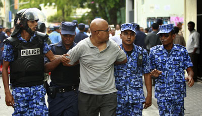 A protester is arrested during ongoing demonstrations in Male. (AP/Sinan Hussain)