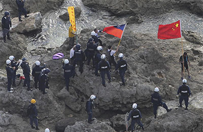 The Taiwanese flag was obscured or erased in some Chinese publications that published photos like this one, of activists being arrested by Japanese police as they  landed on islands claimed by China, Japan, and Taiwan. (AP/Yomiuri Shimbun, Masataka Morita)