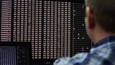 An analyst looks at malware code in a lab. (Reuters/Jim Urquhart)
