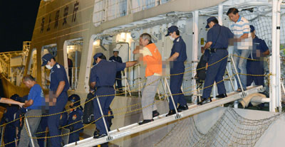 Chinese activists are escorted as they disembark from a Japan Coast Guard patrol ship. (Reuters/Kyodo)