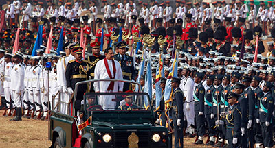 Sri Lankan President Mahinda Rajapaksa, in white, inspects a parade May 19 marking the third anniversary of the defeat of Tamil Tiger separatists. (Reuters/Dinuka Liyanawatte)