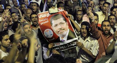 Supporters raise a photo of President Morsi. (AP/Amr Nabil)
