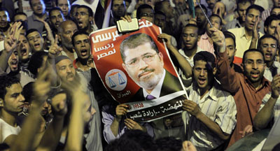 Supporters raise a photo of President Morsi. (AP/Amr Nabil)