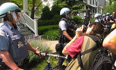 A journalist photographs at a protest against the NATO Summit in May 2012 in front of Chicago Mayor Rahm Emanuel's home. (Mickey H. Osterreicher)