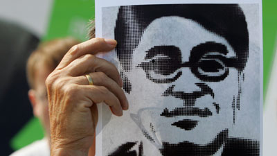 A protester holds a poster depicting jailed journalist Shi Tao. (AP/Miguel Villagran)