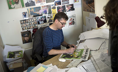 Stéphane Charbonnier, publisher and cartoonist of Charlie Hebdo, draws on the magazine's latest issue, which features several cartoons caricaturing the Prophet Muhammed. (AFP/Fred Dufour)