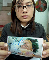 Blogger Trinh Kim Tien shows a photo of her father after he was beaten by police. (AFP/Ian Timberlake)