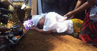 The wife of journalist Daudi Mwangosi weeps at his grave. Mwangosi was killed in a scuffle with police on Sunday. (Gustav Chahe)