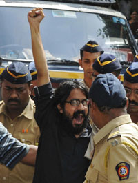 Aseem Trivedi shouts slogans as he is escorted by police outside court. (Reuters)