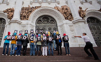 A security guard at the Christ the Saviour Cathedral, right, runs toward Pussy Riot supporters holding Cyrillic letters reading 'Blessed are the Merciful' in Moscow on Aug. 15. (AP/Novaya Gazeta, Yevgeny Feldman)