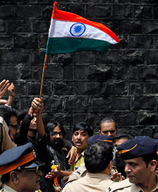 Indian political cartoonist Aseem Trivedi waves the national flag after being released from jail on bail in Mumbai on September 12. (AP/Rajanish Kakade)