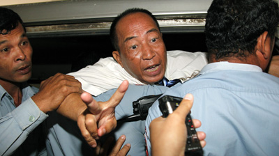 Police escort Mam Sonando into a car after a court sentenced him to 20 years. (AFP)