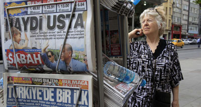 A passer-by looks at Turkish newspapers at a kiosk in Istanbul. (AP/Thanassis Stavrakis)