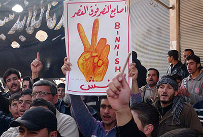 This image provided by Edlib News Network shows an anti-Syrian regime protester holding up a placard reading: 'the victory fingers over the Place (the presidential palace),' during a demonstration at Binnish village, Idlib province, on Friday. (AP/Edlib News Network ENN)