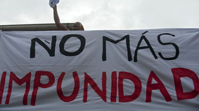 """A woman stands next to a banner reading """"No more impunity"""" in Colombia. (AFP/Raul Arboleda)"""