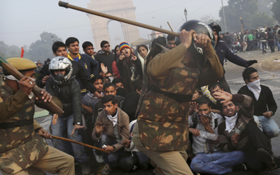 Police beat protesters near India Gate, New Delhi. (AP/Kevin Frayer)