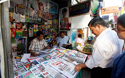 Customers buy weekly news journals at a roadside shop in Yangon, Myanmar, Friday. Authorities said they will allow private daily newspapers starting in April for the first time since 1964. (AP/Khin Maung Win)