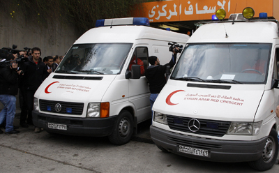 Ambulances carry the bodies of Marie Colvin and Rémi Ochlik, who were killed in government shelling in Syria. (Reuters/Khaled al-Hariri)