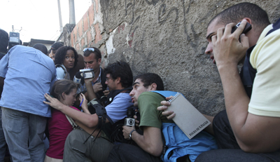 Journalists take cover in a shootout between police and drug traffickers in Brazil. (AP/Silvia Izquierdo)