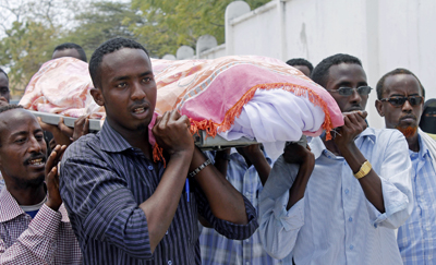 Somalis carry the body of journalist Abdisatar Dahir Sabriye, who was killed in an attack at a Mogadishu café in September. (AFP/Mohamed Abdiwahab)