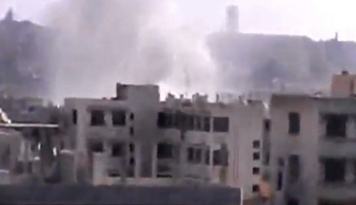 An image from a video published by the Shaam News Network shows smoke rising from buildings in Homs destroyed by government shelling. (AP/Shaam News Network)