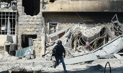 Un periodista esquiva disparos de armas de fuego en la ciudad de Alepo, en Siria. (AFP/Tauseef Mustafa)