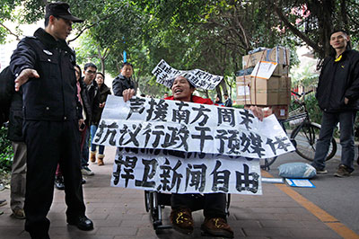 A supporter of Southern Weekly newspaper outside its headquarters in Guangzhou holds banners reading, 'Support Southern Weekly. Protest intervention in media. Defend press freedom.' (AP/Vincent Yu)