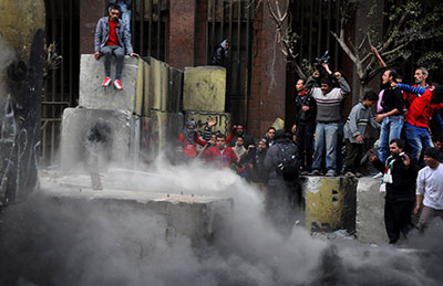 Egyptian protesters tear down a cement wall blocking them from the parliament and cabinet buildings in Cairo on Thursday. (AP/Hussein Tallal)