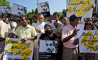Journalists, rights activists, and opposition lawmakers, with Sandya Eknelygoda in the center, protest attacks on journalists and authorities' failure to punish the culprits in Colombo Tuesday. (AP/Gemunu Amarasinghe)