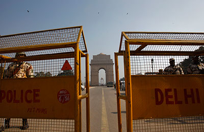 Indian policemen stand guard near India Gate in New Delhi. A magistrate ruled Monday that the media will not be allowed to attend the trial of five men accused of raping and killing a young student. (AP/Tsering Topgyal)