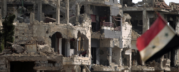 A flag flies next to a building destroyed by shelling in the city of Baba Amr. (AFP/Joseph Eid)