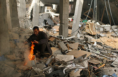 A Palestinian warms himself at the rubble of his house that witnesses said was destroyed in an Israeli air strike during a week of fierce fighting in Gaza City in November. (Reuters/Mohammed Salem)