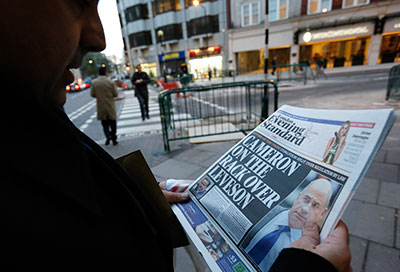 A man reads a newspaper article about Lord Justice Brian Leveson's report on media practices in central London November 29, 2012. (Reuters/Olivia Harris)