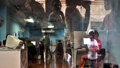 Ciudadanos cubanos esperan para obtener acceso a la Web en un café Internet de La Habana. (AFP)