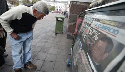 Un transeúnte se detiene a leer un diario el día después de la reelección de Correa. (AFP/Rodrigo Buendia)