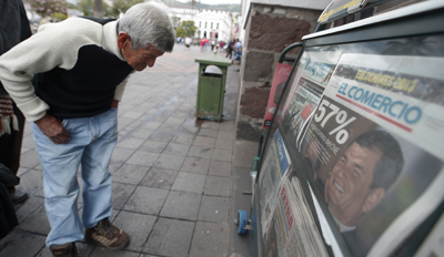 A passer-by stops to look at a newspaper the day after Correa is re-elected. (AFP/Rodrigo Buendia)