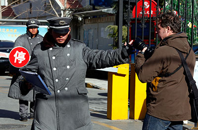 A security guard confronts a photographer at the entrance of the compound where Liu Xia lives in Beijing December 10, 2010, after her husband was awarded the Nobel Peace Prize. (Reuters/David Gray)