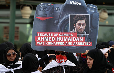 A Bahraini anti-government protester carries a sign with the picture of a jailed photographer during a march in Karranah, Bahrain, on Friday. (AP/Hasan Jamali)