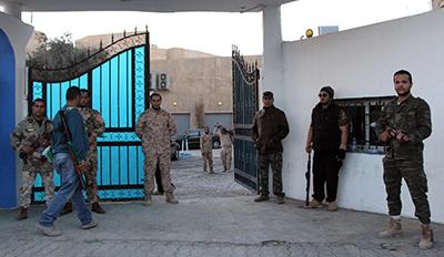 Guards stand outside Alassema TV station in Tripoli. (AFP/Mahmud Turkia)
