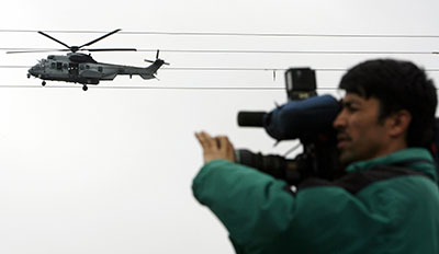 An Afghan journalist films in Kabul as a military helicopter flies above. (Reuters/Ahmad Masood)