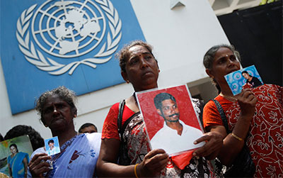 Sri Lankan Tamils hold photos of family members who disappeared in the war between Sri Lankan government troops and Tamil Tiger rebels as they wait to hand over a petition at the U.N. office in Colombo on March 13. (Reuters/Dinuka Liyanawatte)
